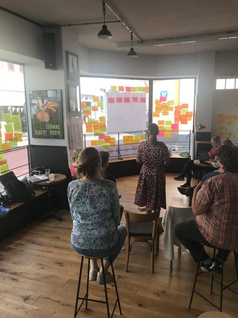 Die fairkehr-Redaktion beim Brainstorming. An einer Wand hängen viele bunte Zettel rund um ein großes weißes Plakat.